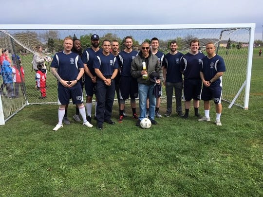 The Honey Badgers present a third-place trophy to Detroit Police Chief James Craig Saturday, May 11 at Patton Park after they played in a tournament against departments around the world.