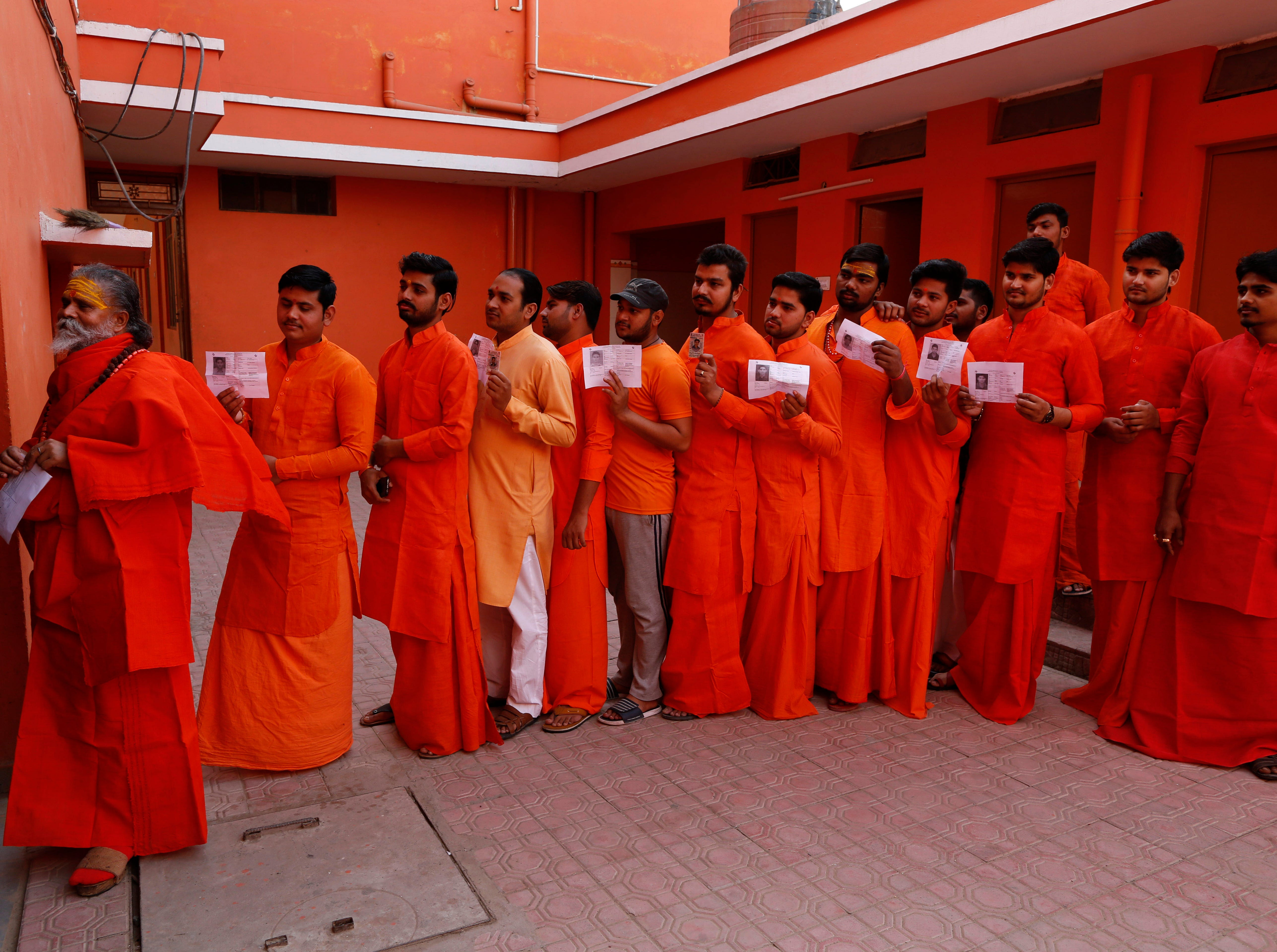 Hindu holy men, stand in a queue to cast their votes at a polling station in Prayagraj, Uttar Pradesh state, India , Sunday, May 12, 2019. Indians are voting in the next-to-last round of 6-week-long national elections, marked by a highly acrimonious campaign with Prime Minister Narendra Modi flaying the opposition Congress party rival Rahul Gandhi's family for the country's ills.