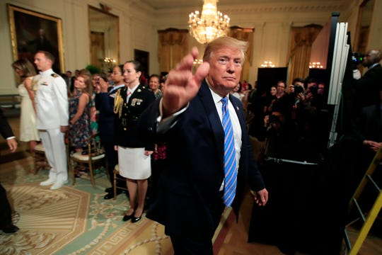President Donald Trump waves as he leaves the East Room during a celebration of military mothers with first lady Melania Trump at the White House in Washington, Friday, May 10, 2019.