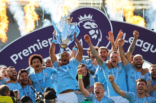 Manchester City's Vincent Kompany lifts the English Premier League trophy after the match against Brighton.