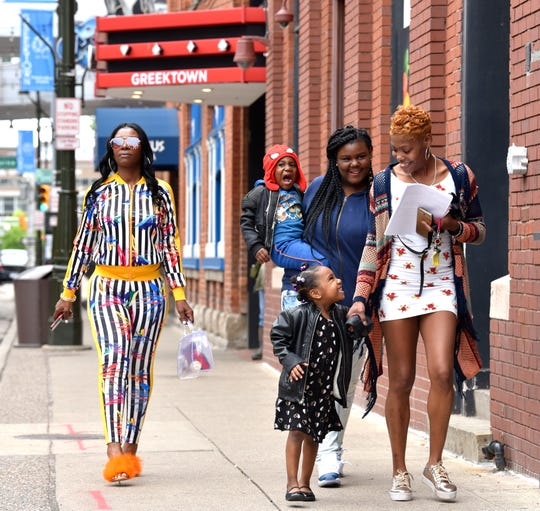 Rokiea Rivers, right, smiles down at her daughter, Jernee Caster, 4, as Katisha Long, left, walks with her son, King Caster, 3, and daughter, Wynter Dhue, all of Detroit, as they head to the Greektown People Mover station.