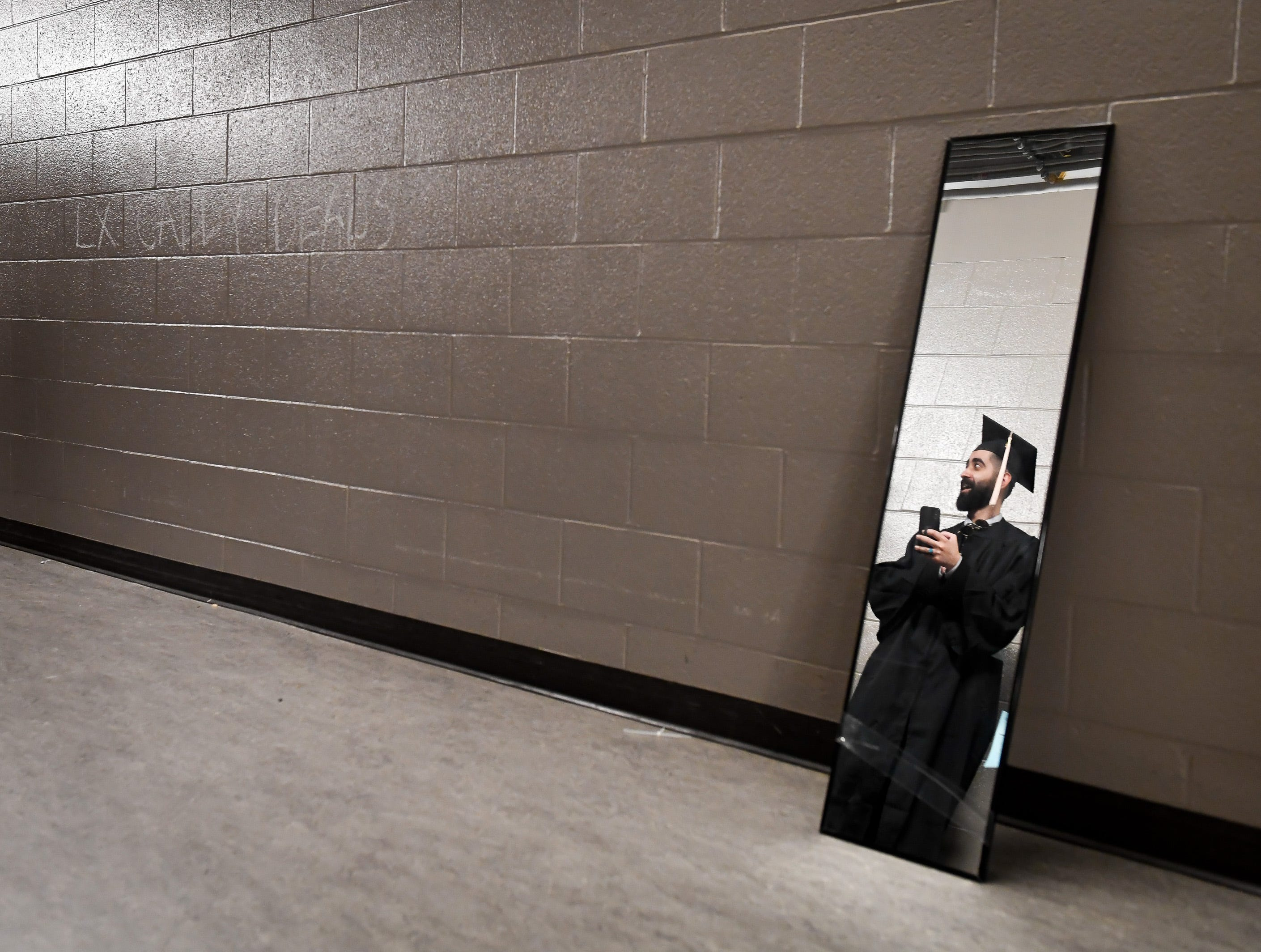 Fahad Mansour Alkhaliwi, Saudi Arabia,  is reflected in one of several mirrors for graduates waiting for the start of the University of Evansville's 161st commencement ceremony held at the Ford Center Saturday, May 11, 2019.