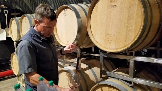 Bill Oliver, CEO and founding family member of Oliver Winery, pulls a sample of an estate-grown Crimson Cabernet wine.