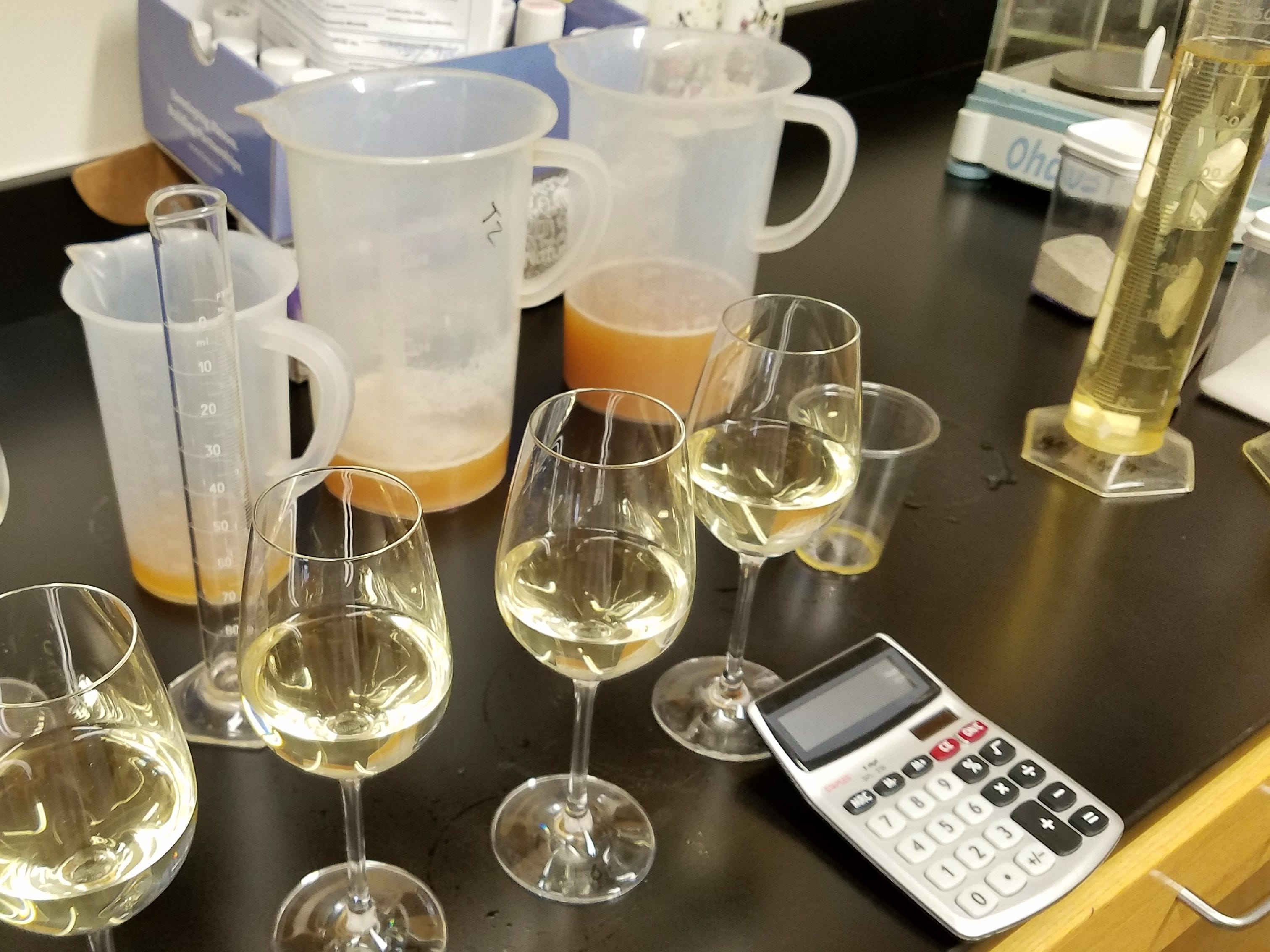 Glasses of Moscato wine and pitchers of apple juice in the lab at Oliver Winery in Bloomington.
