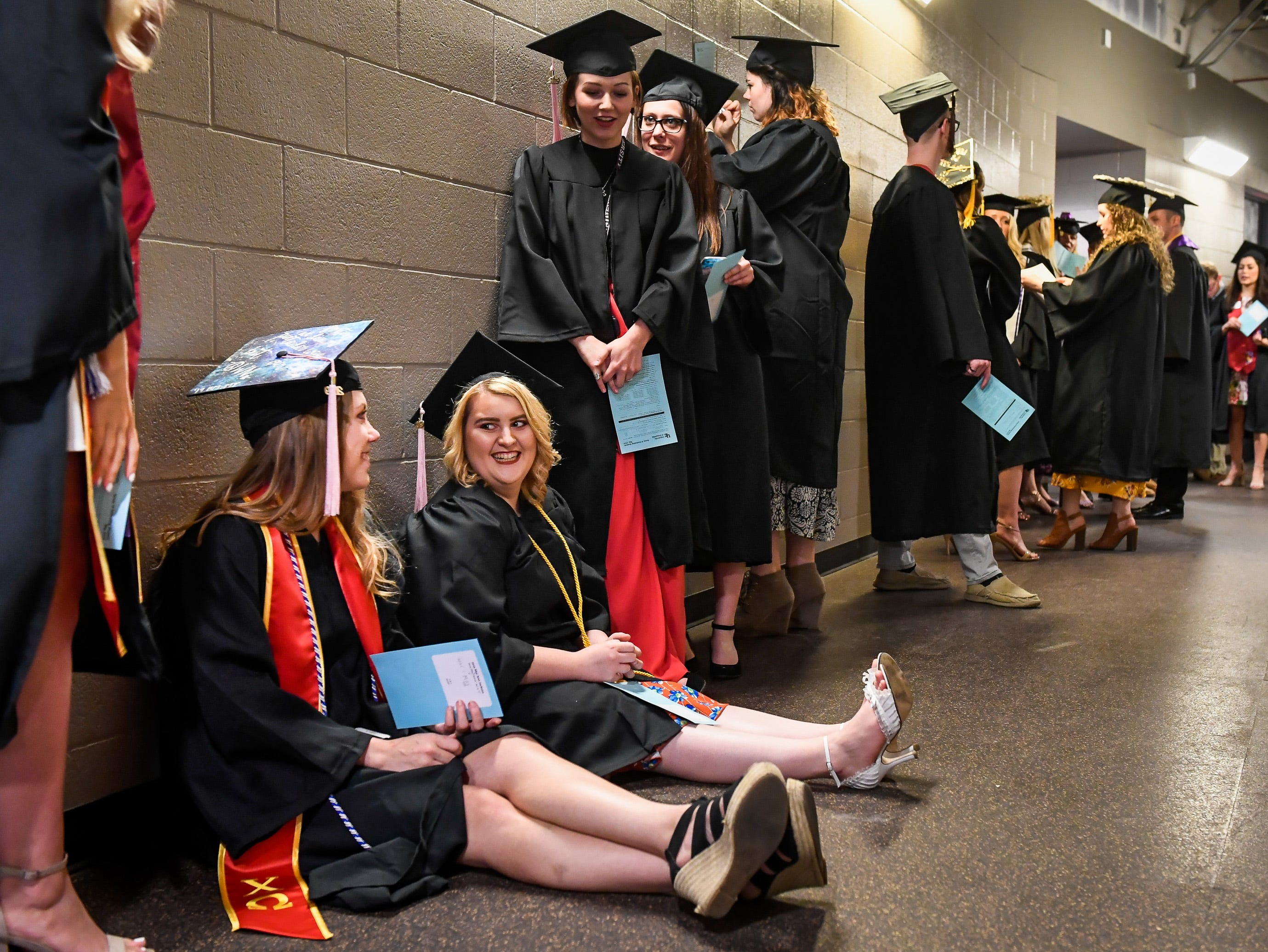 Soon to be graduates, Jana Jackson, left, and April Kuhnert rest on the floor as they cue up in the arena tunnel for the University of Evansville's 161st commencement ceremony held at the Ford Center Saturday, May 11, 2019.