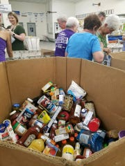 Workers and volunteers at the Fort Myers Beach Post Office load items during Saturday's Stamp Out Hunger food drive. More than 185,000 pounds of food were collected.