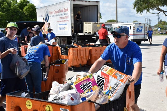 Workers and others at the Cape Coral Central Post Office load food items gathered during Saturday's Stamp Out Hunger program to be taken to the Harry Chapin Food Bank's Fort Myers Distribution Center . Te program collected more than 185,000 pounds of food.