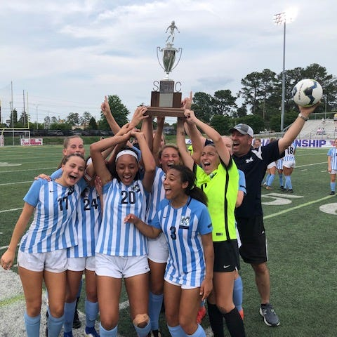 J.L. Mann girls soccer players raise their third straight state championship trophy after defeating Wando Saturday in Columbia