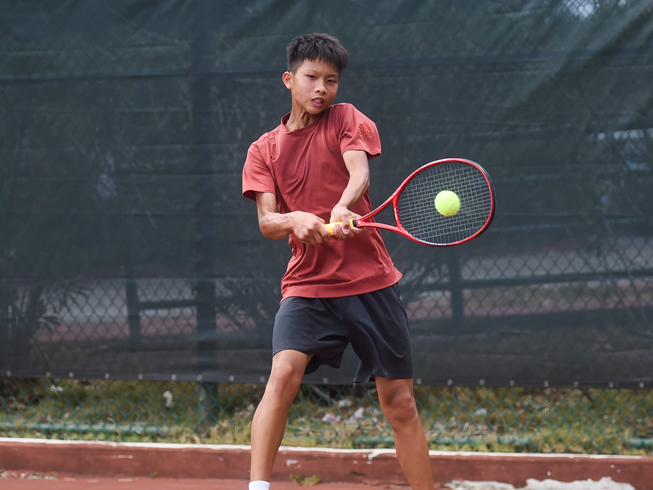 Yu-Shun Lai delivers a two-handed forehand shot during a 2019 Chuck E Cheese ITF World Tennis Tour Juniors qualifying match at the Hilton Guam Resort and Spa in Tumon, May 12, 2019.