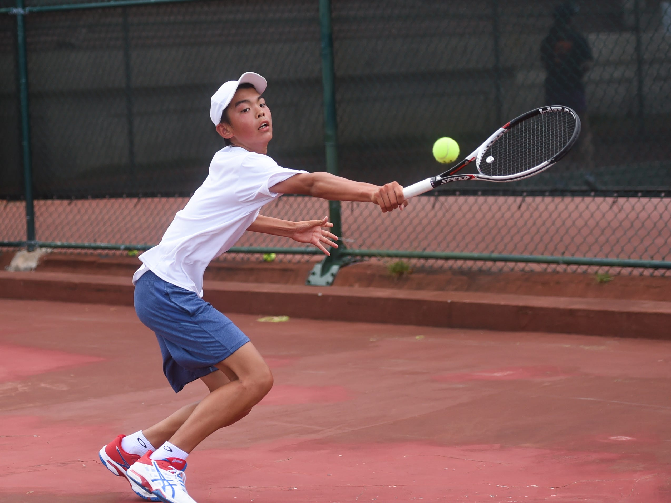 Kohdai Sasaki goes for a backhand shot during a 2019 Chuck E Cheese ITF World Tennis Tour Juniors qualifying match at the Hilton Guam Resort and Spa in Tumon, May 12, 2019.