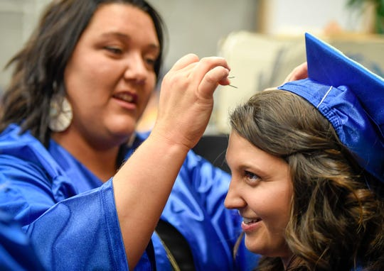 Cierra Vos helps Hannah Gibbs with her mortarboard before the start of the Henderson Community College commencement ceremony held at the Preston Arts Center Friday evening.