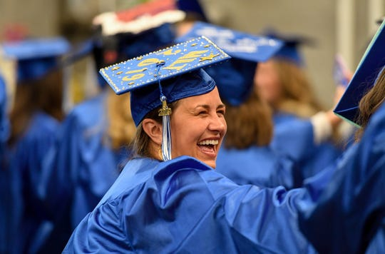 Amber Tichenor laughs with friends as graduates gather before the start of the Henderson Community College commencement ceremony held at the Preston Arts Center last Friday evening.