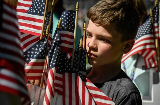 In May 2019, North Middle School student Brayden Knott carries an arm load crosses as students help set up the crosses honoring Henderson County veterans who have passed away.