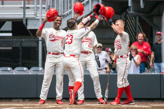 Todd Lott (9), Orynn Veillon (21) and Daniel Lahare (26) congratulate UL senior catcher Handsome Monica (23) after his three-run homer in Sunday's Senior Day 11-5 win over Georgia State.