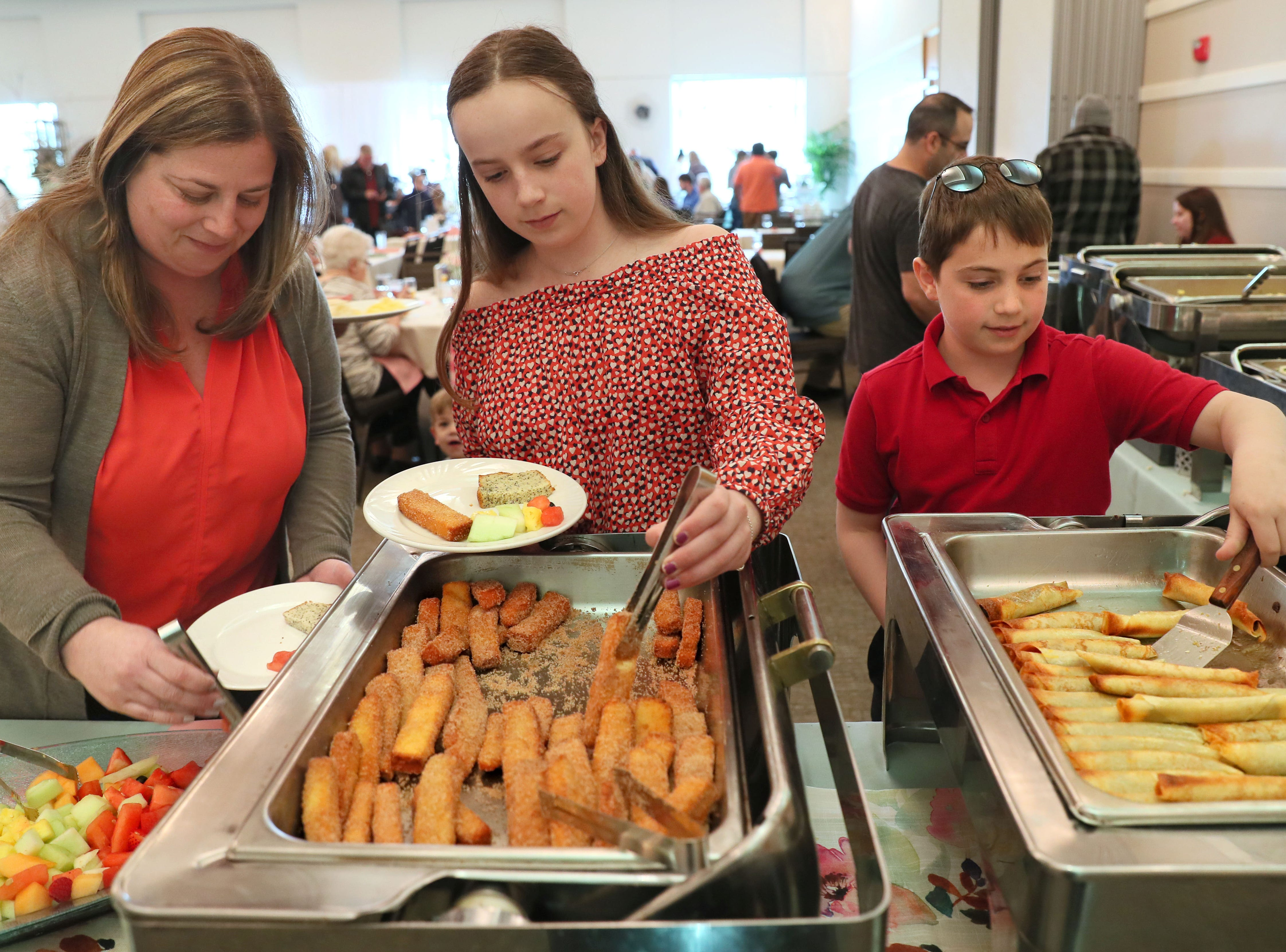 Stephanie Dykeman, left, of Bayside and her two children, Grace, 12, and Max, 10, help themselves to the brunch offered at the Education and Visitor Center.
