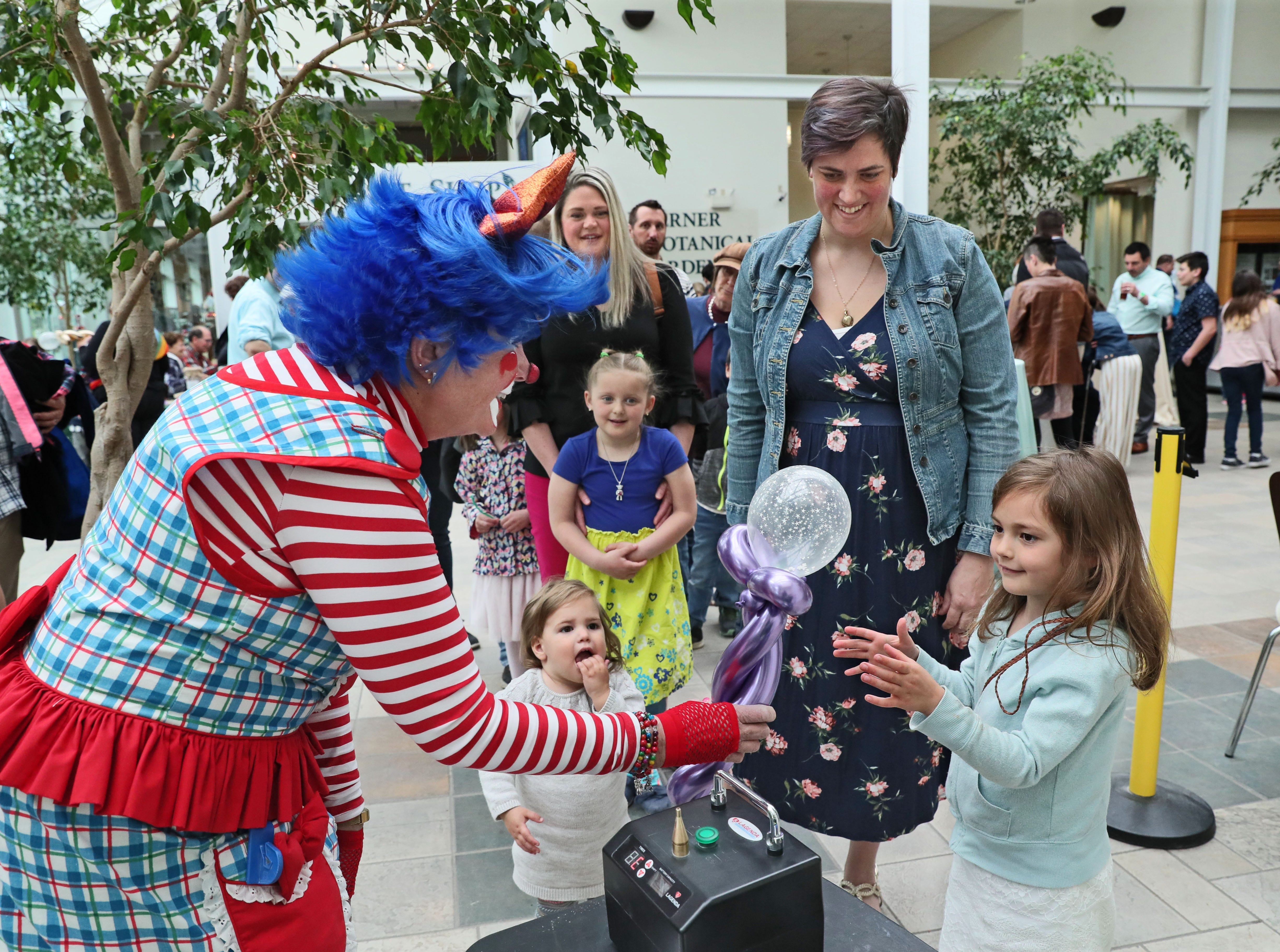 Miss Sparkle The Clown makes artistic balloon creations for children and their mothers.  Jennifer Cera (center) of Wauwatosa is with her two children, Ramona, 5, getting her balloon, and Margot, 1, lower center.  At rear waiting in line is Brooke Moersfelder of Greenfield and her daughter Rose, 5.