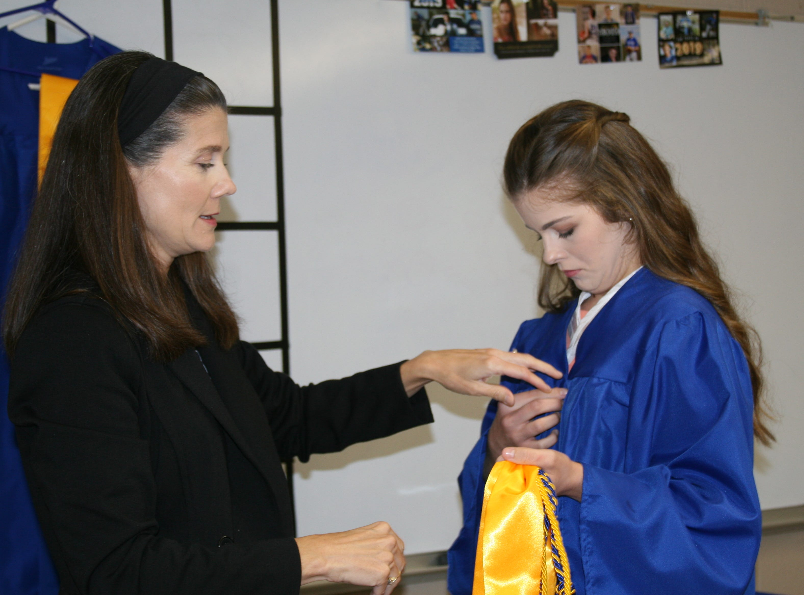 Cotter Senior Class Sponsor Amy Manns helps her daughter, Claire Christal Manns, a summa cum laude graduate, with her graduation gown.