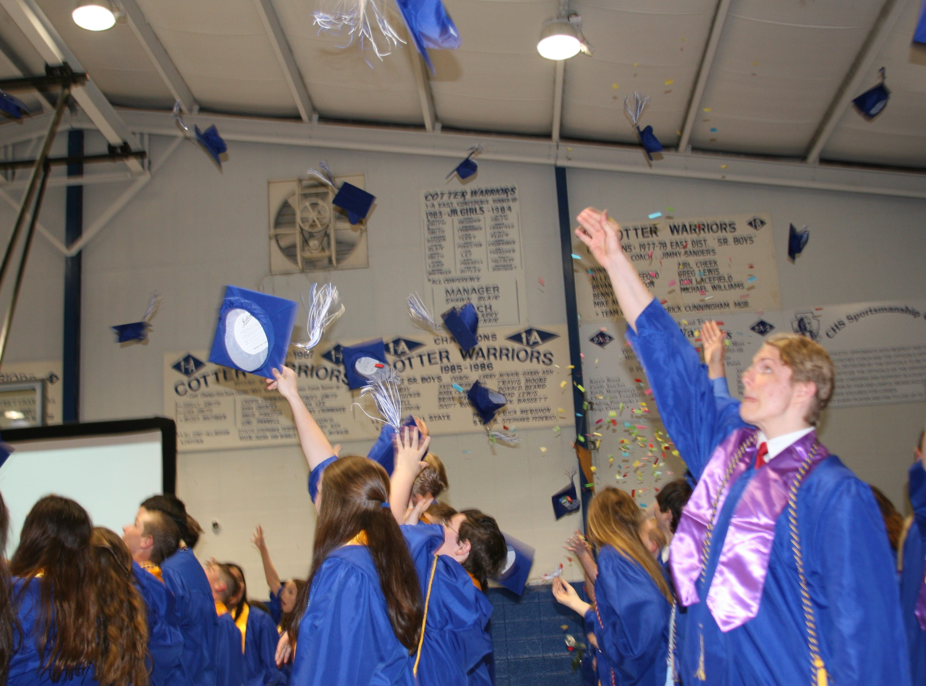 Joyful graduates of Cotter High School's 2019 class toss their mortar boards in the air in celebration of their achievements.