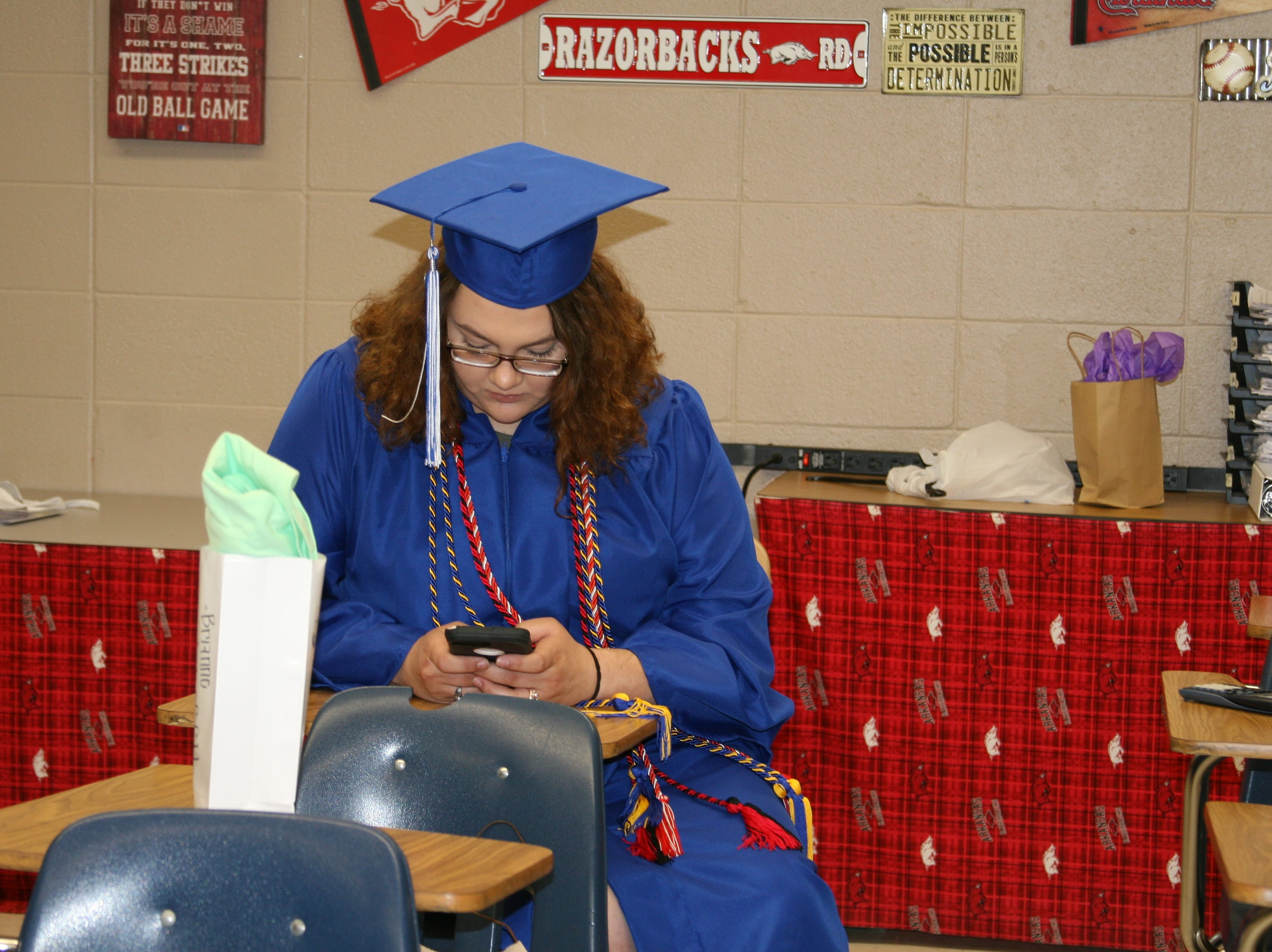 Students took time to check their phones and relax before the 2019 Warrior graduation at Cotter High School.