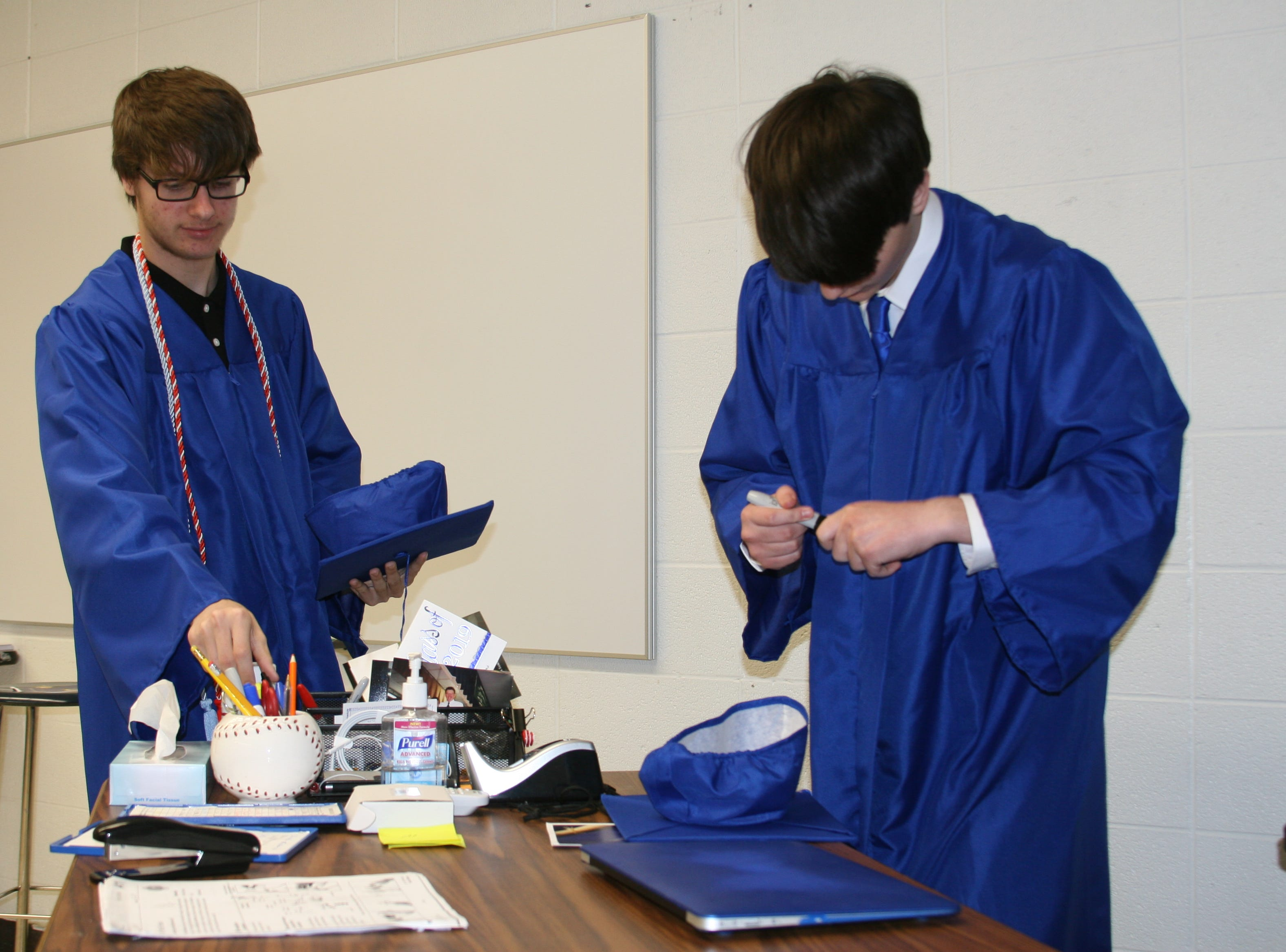 Students were advised to write their names in their mortar boards before entering the gymnasium for graduation ceremonies. It is tradition for the graduates to toss their caps after they've received their diplomas and they can often end up with different owners at the end of the festivities.