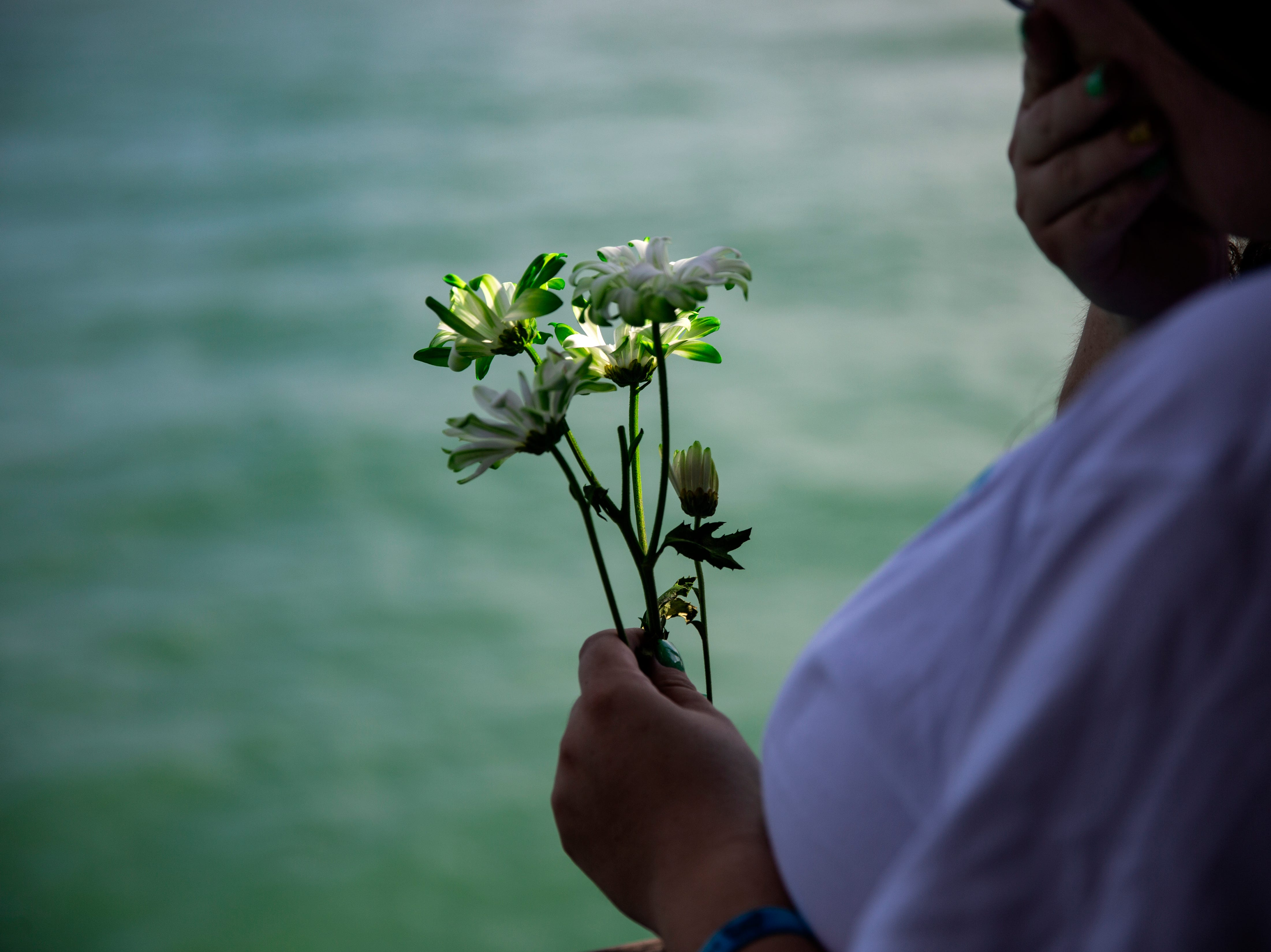 Holly Vingson prepares to drop flowers in to the Gulf in memory of her 6-year old son AJ Ruiz during the annual Moms' Celebration of Life event,, Sunday, May 12, 2109, at the Naples Pier.
