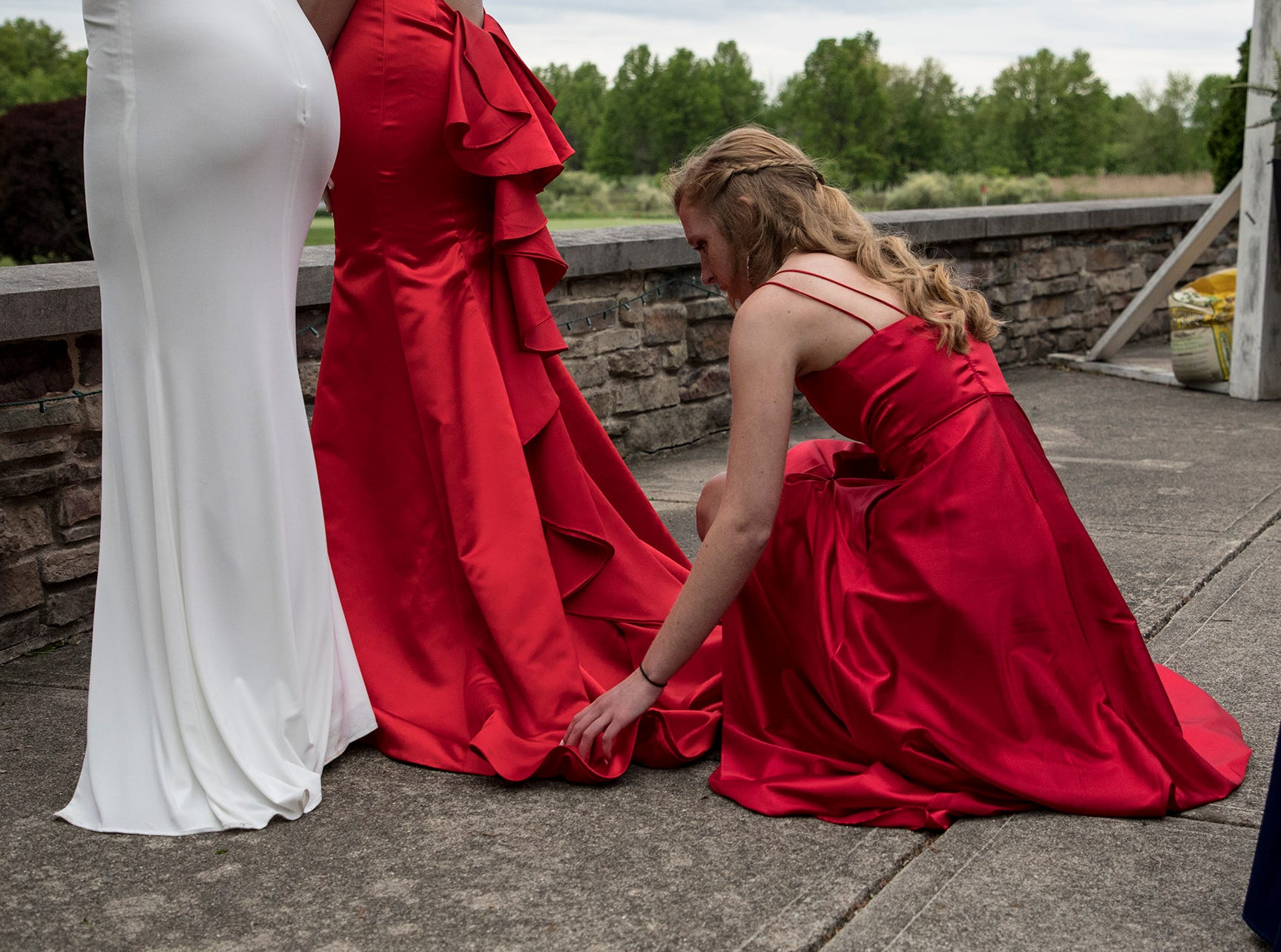 Sidney Blair fixes the dresses of her friends, Ryan Helmke and McKenzie Andrix before their friend, Reagan Helmke, takes their photo at the 2019 Johnstown prom at the Medallion Club in Westerville.