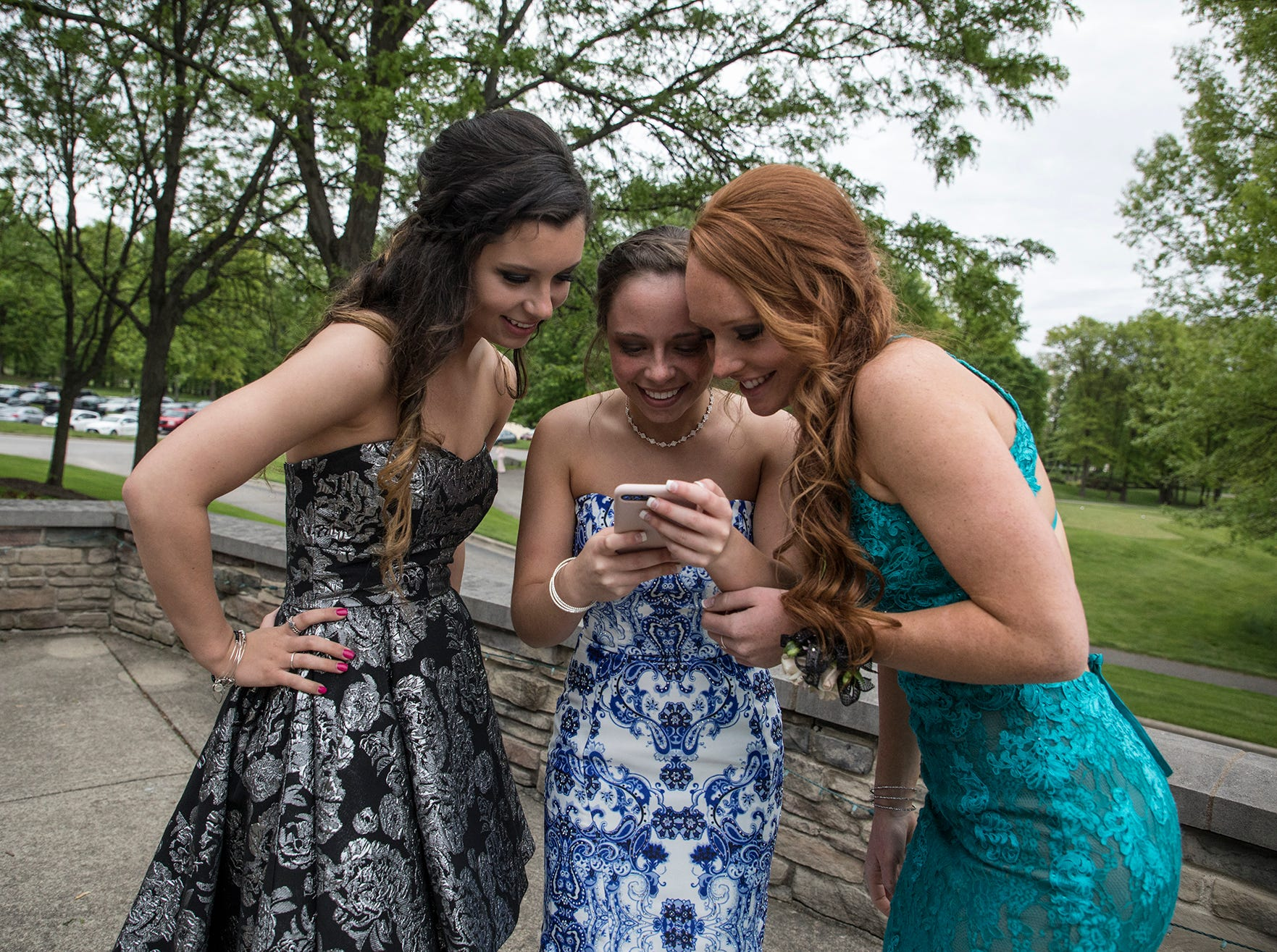 Karlee Psurny, Maddie Lester, Jenna Beebe look at a photo at the 2019 Johnstown prom at the Medallion Club in Westerville.