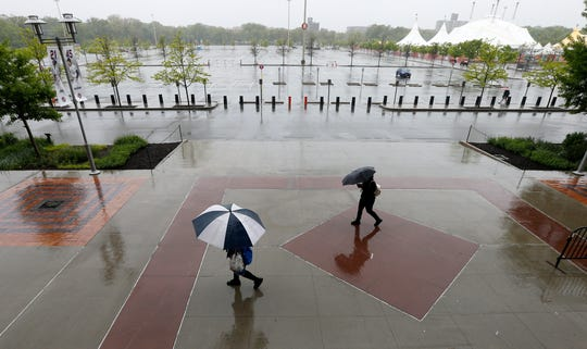 Pedestrians are seen walking outside of Citi Field after a game between the New York Mets and the Miami Marlins was postponed due to rain on May 12, 2019 in New York City.