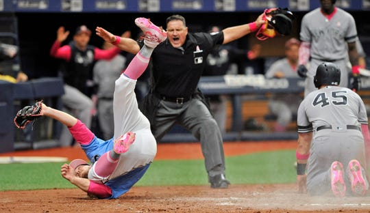 Home plate umpire Tony Randazzo, center, makes the call as Tampa Bay Rays pitcher Ryne Stanek, center, tumbles after trying to tag out New York Yankees' Luke Voit (45) in a collision at the plate during the eighth inning of a baseball game Sunday, May 12, 2019, in St. Petersburg, Fla. Voit scored on a wild pitch thrown by Stanek.