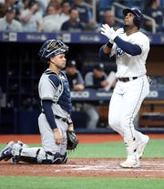 May 11, 2019; St. Petersburg, FL, USA; Tampa Bay Rays third baseman Yandy Diaz (2) reacts at home plate as New York Yankees catcher Gary Sanchez (24) looks on as he hits a home run during the third inning at Tropicana Field.