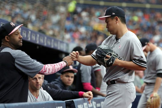 May 12, 2019; St. Petersburg, FL, USA; New York Yankees starting pitcher Masahiro Tanaka (19) celebrates with Yankees pitcher CC Sabathia (52) at the end of the first inning against the Tampa Bay Rays at Tropicana Field.