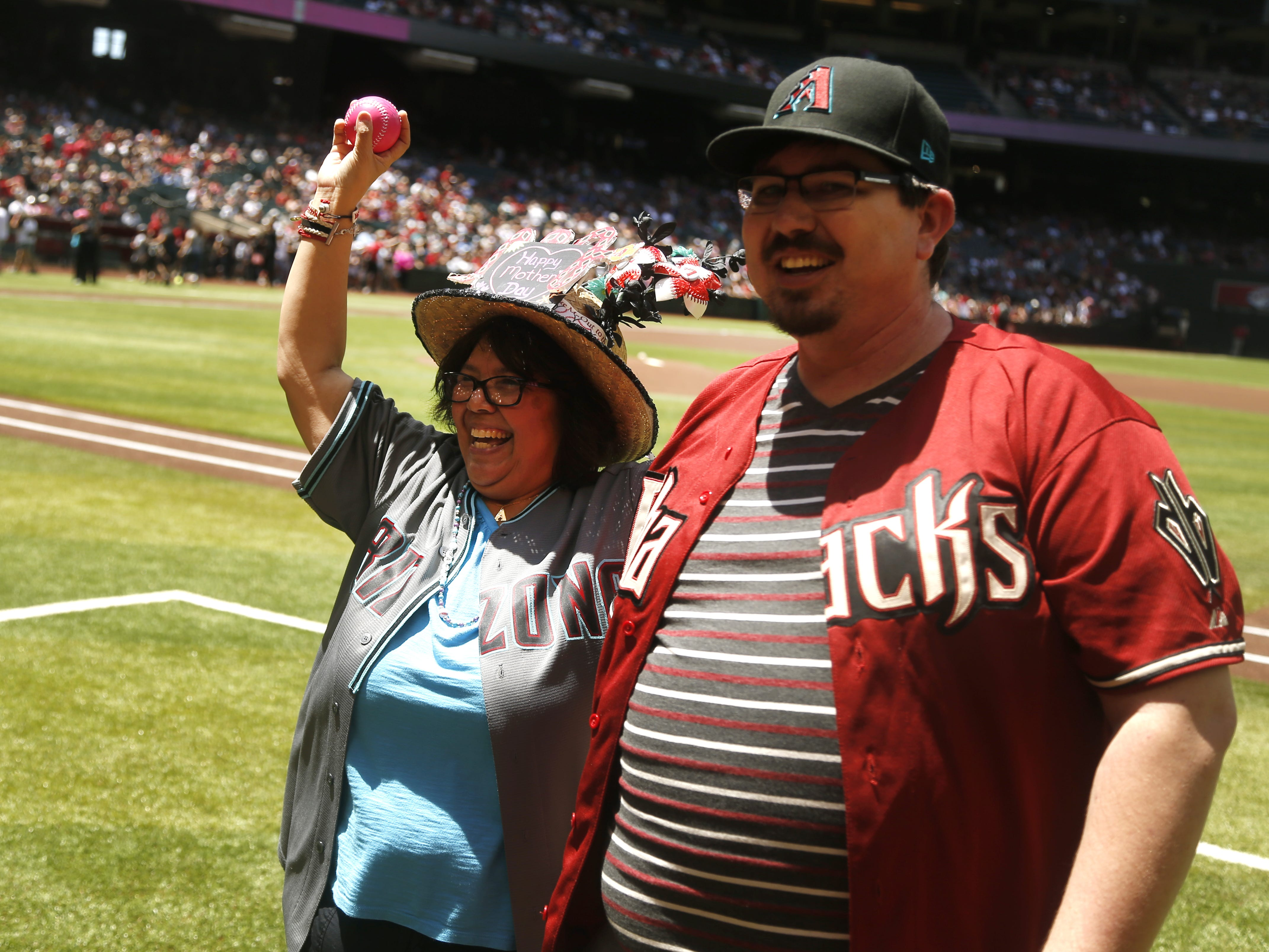 """Melissa Boesen celebrates with her son Chris Boesen after throwing out a """"first pitch"""" with other mom's on Mother's Day before a Diamondbacks game against the Braves at Chase Field in Phoenix, Ariz. on May 12, 2019."""