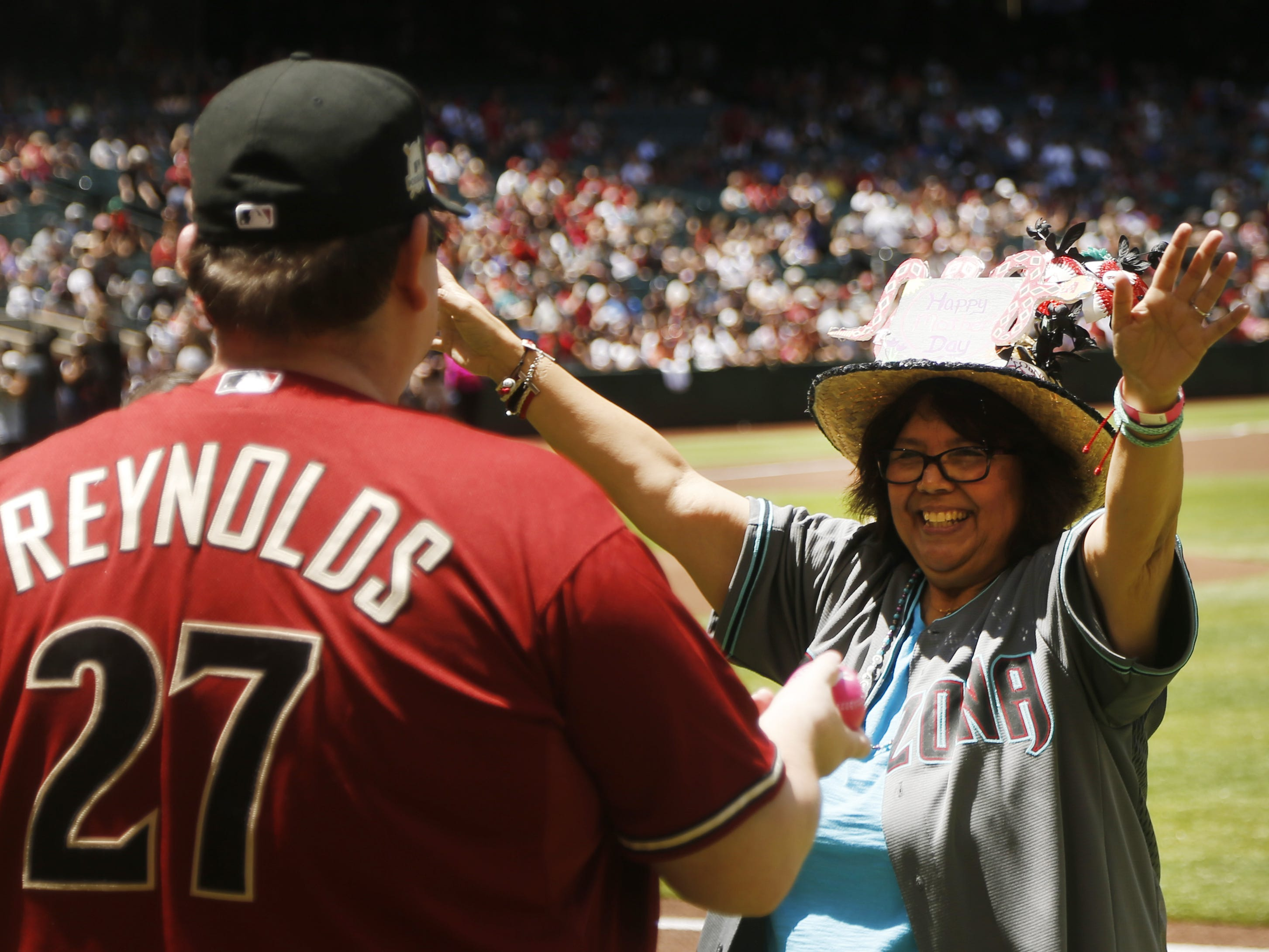 "Melissa Boesen celebrates with her son Chris Boesen after throwing out a ""first pitch"" with other mom's on Mother's Day before a Diamondbacks game against the Braves at Chase Field in Phoenix, Ariz. on May 12, 2019."