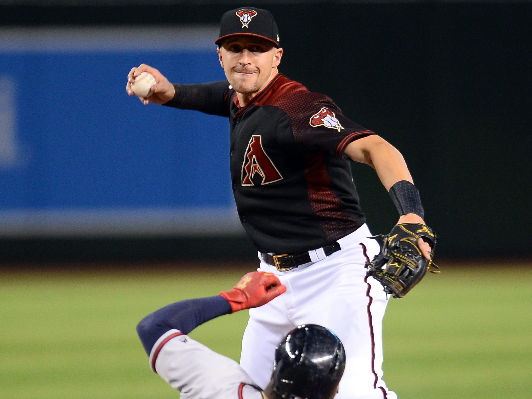 May 11, 2019; Phoenix, AZ, USA; Arizona Diamondbacks shortstop Nick Ahmed (13) throws to first base after forcing out Atlanta Braves second baseman Ozzie Albies (1) at second during the eighth inning at Chase Field.