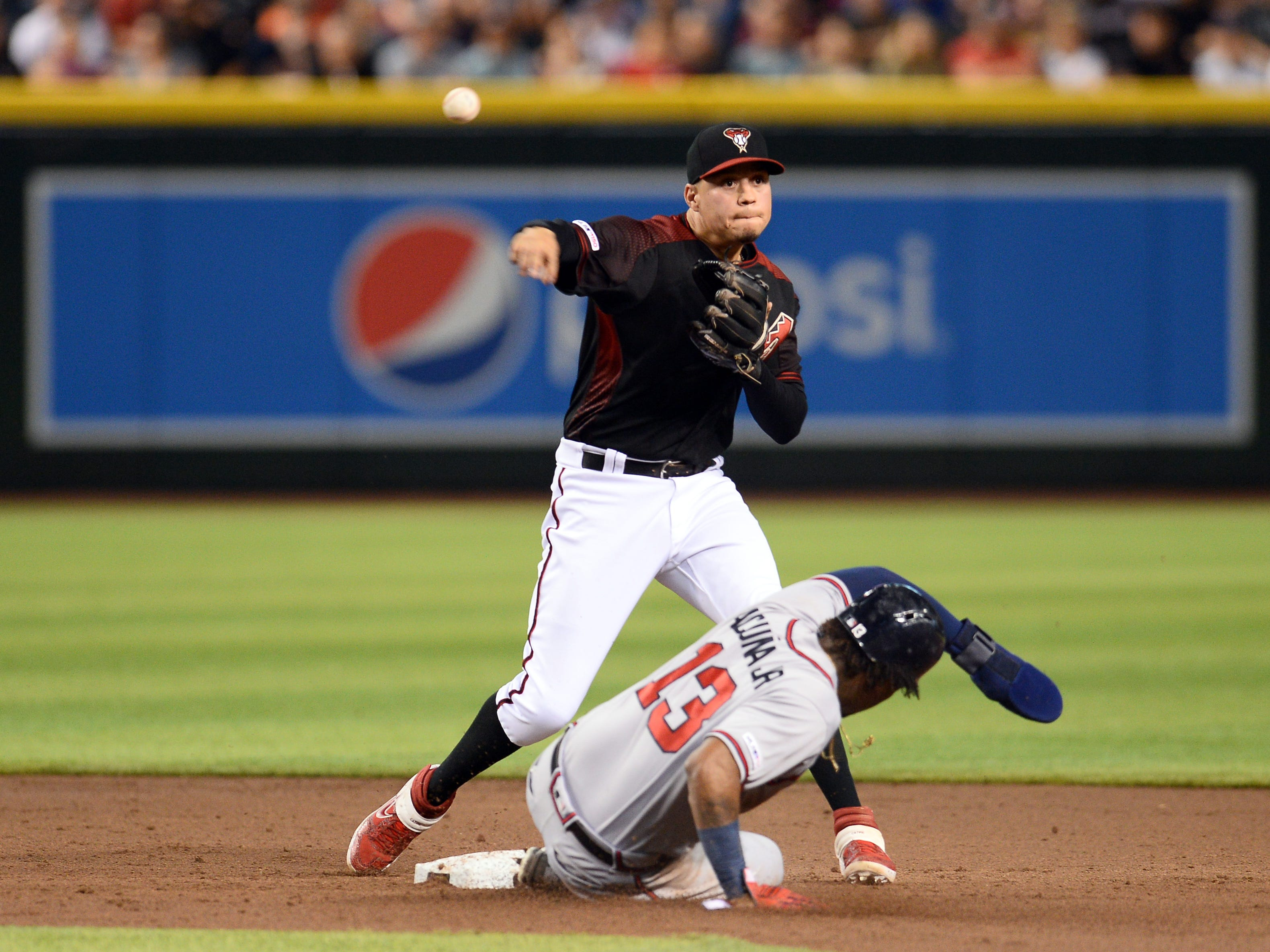 May 11, 2019; Phoenix, AZ, USA; Arizona Diamondbacks third baseman Wilmer Flores (41) throws to first after forcing out Atlanta Braves left fielder Ronald Acuna Jr. (13) at second base during the third inning at Chase Field.
