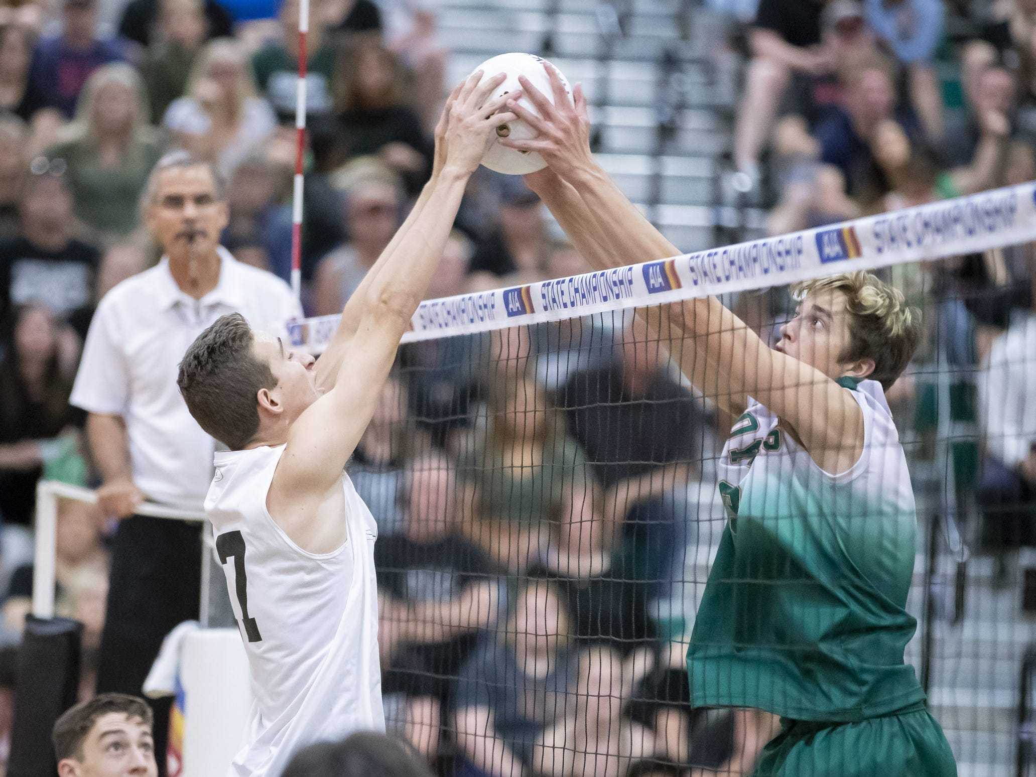 Senior middle blocker Caleb Crook (17) of the Tucson Mountain View Mountain Lions and senior setter Tyler Poulsen (3) of the Campo Verde Coyotes both attempt to set the ball during the 5A Boys Volleyball State Championships at Higley High School on Saturday, May 11, 2019 in Gilbert, Arizona.