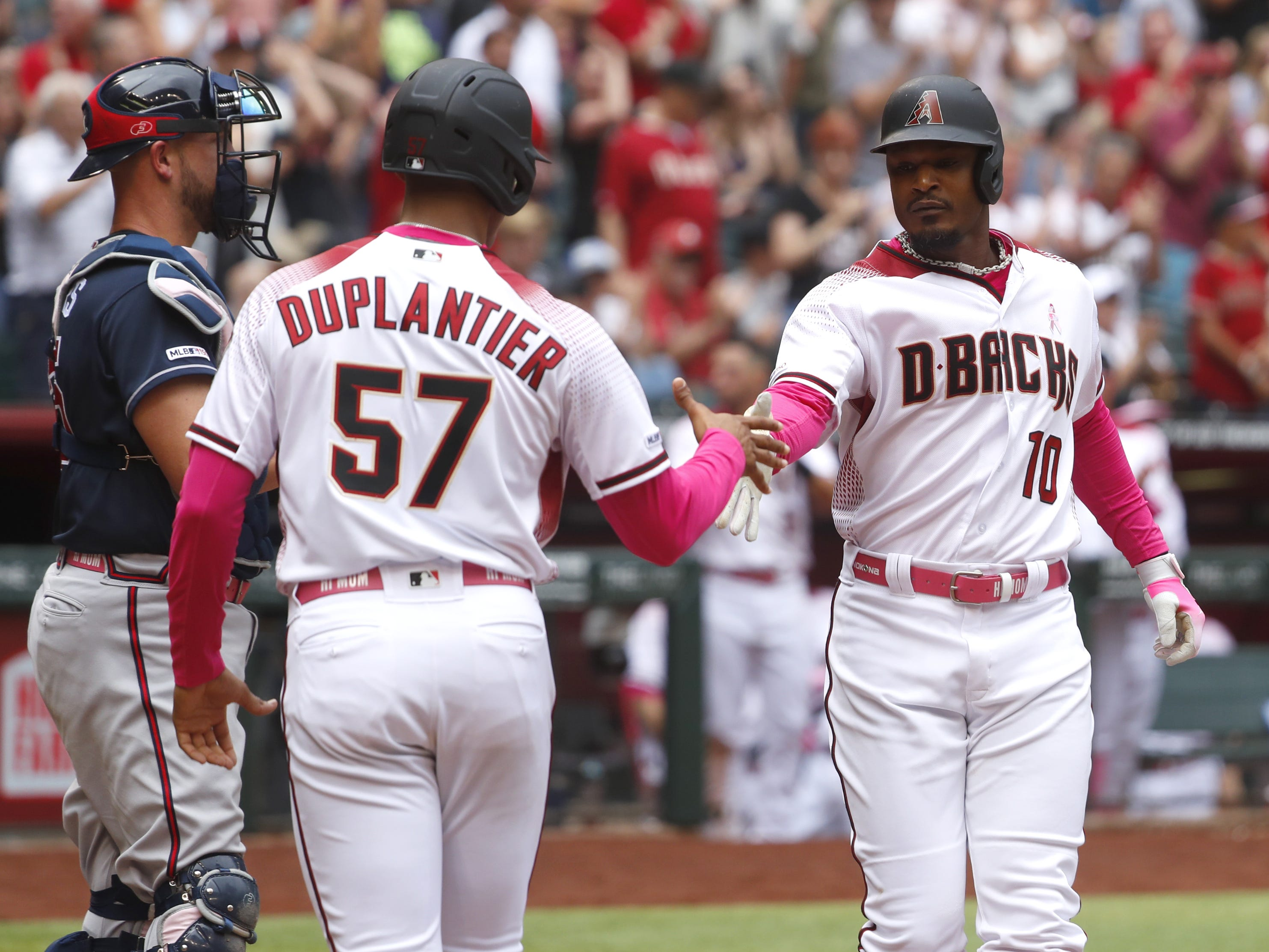 Diamondbacks' Adam Jones (10) celebrates his two-run homer with Jon Duplantier (57) during the fourth inning against the Braves at Chase Field in Phoenix, Ariz. on May 12, 2019.