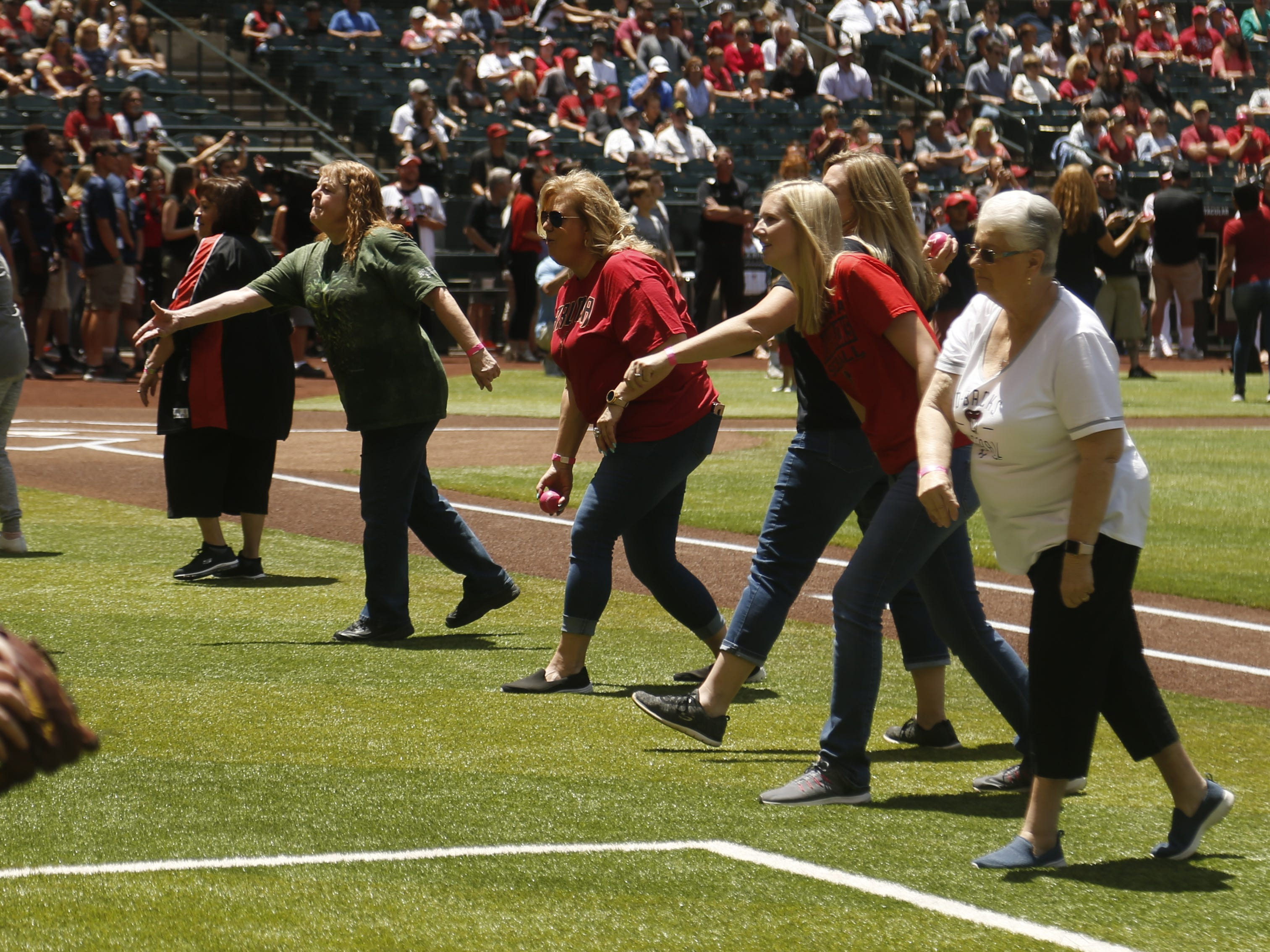 "Mothers throw out ""first pitches"" to their sons and daughters before a Diamondbacks game against the Braves at Chase Field in Phoenix, Ariz. on May 12, 2019."