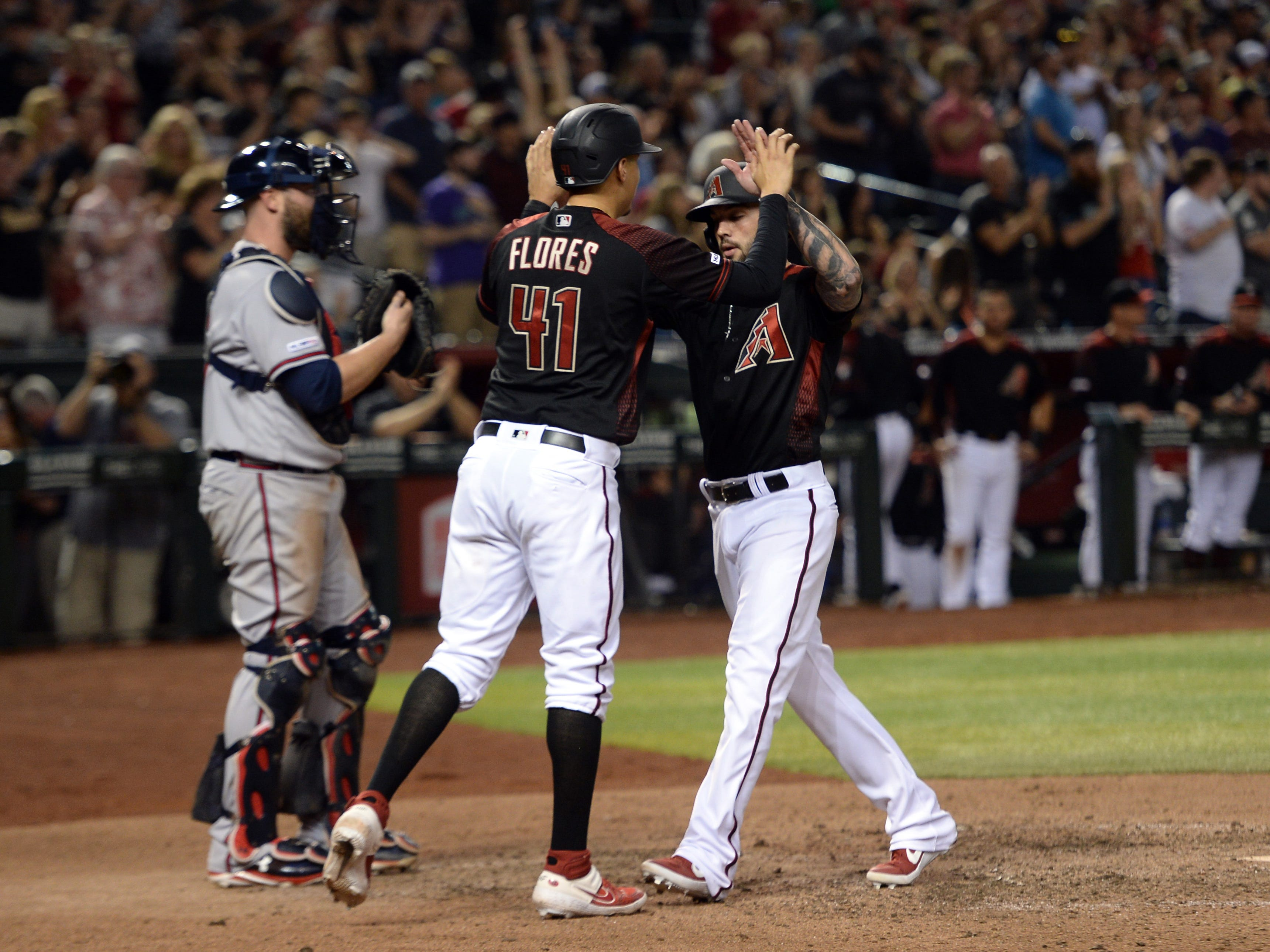 May 11, 2019; Phoenix, AZ, USA; Arizona Diamondbacks third baseman Wilmer Flores (41) and catcher Blake Swihart (19) celebrate at home plate on a two run home run by Swihart against the Atlanta Braves during the eighth inning at Chase Field.