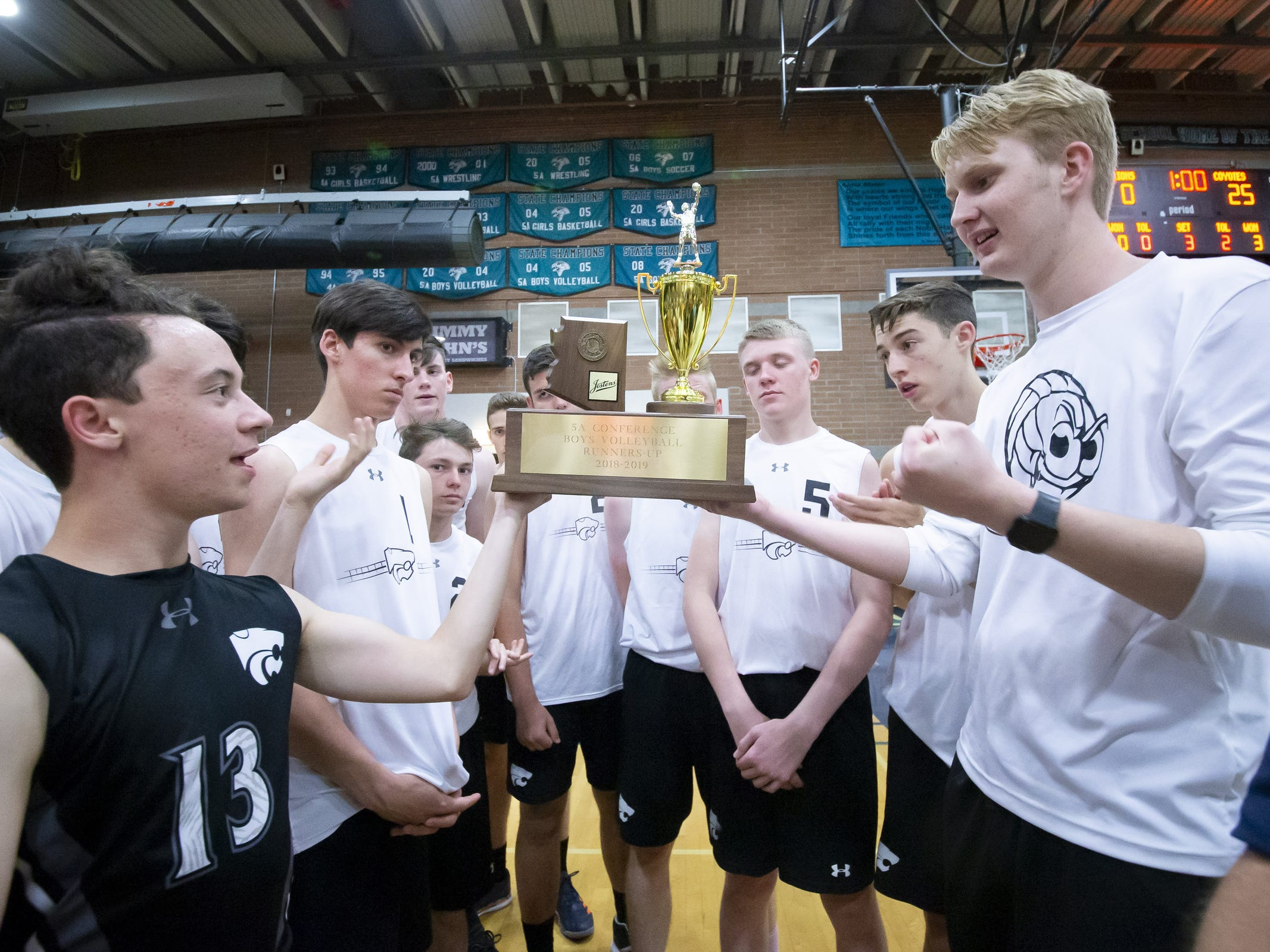 The Tucson Mountain View Mountain Lions hold up their runners-up trophy following their 3-0 loss against the Campo Verde Coyotes in the 5A Boys Volleyball State Championships at Higley High School on Saturday, May 11, 2019 in Gilbert, Arizona.