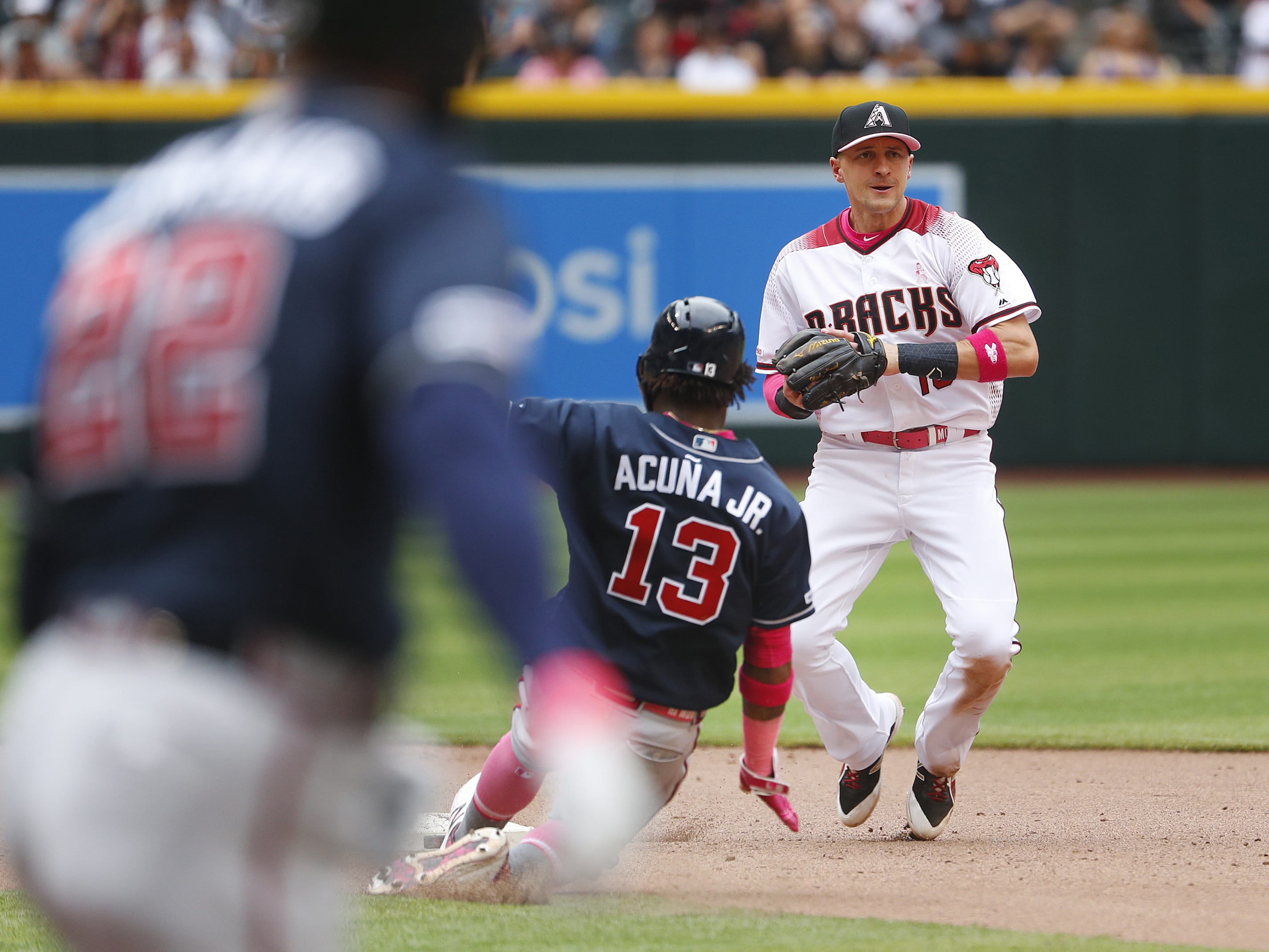 Diamondbacks' Nick Ahmed (13) records a force out on Braves' Ronald Acuna (13) before throwing to first for the double play during the seventh inning at Chase Field in Phoenix, Ariz. on May 12, 2019.