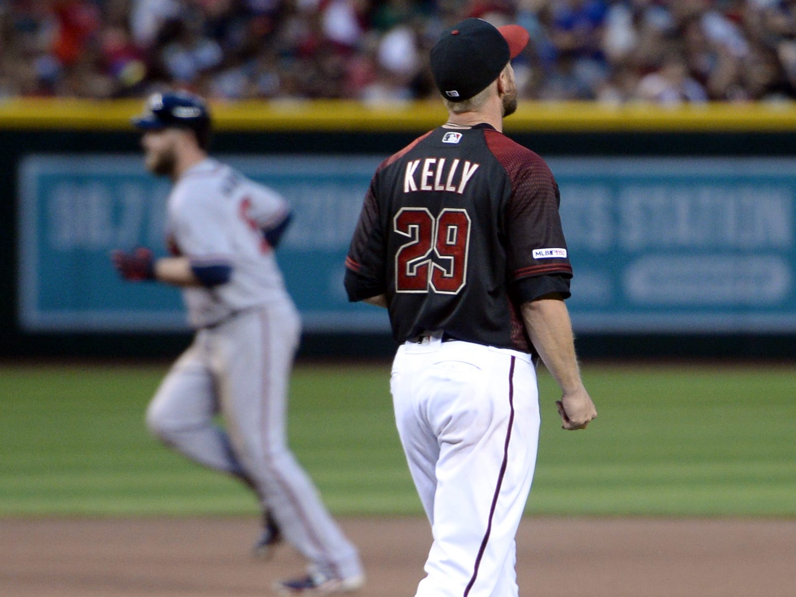 May 11, 2019; Phoenix, AZ, USA; Arizona Diamondbacks starting pitcher Merrill Kelly (29) reacts after giving up a solo home run to Atlanta Braves catcher Brian McCann (16) during the seventh inning at Chase Field.