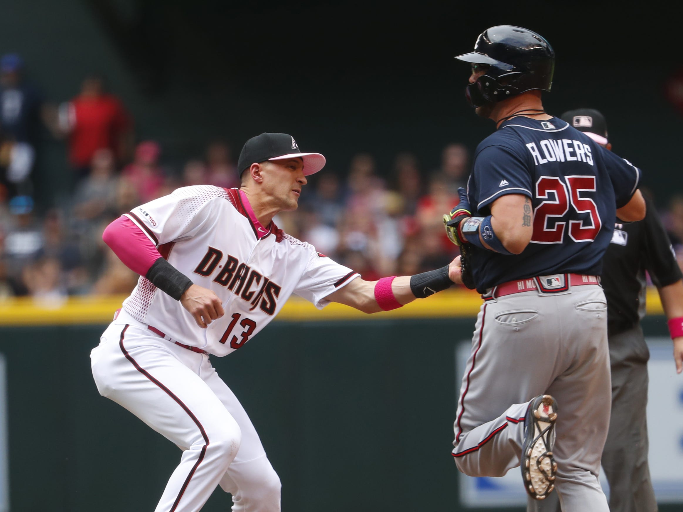 Diamondbacks' Nick Ahmed (13) records an out on Braves' Tyler Flowers (25) after he's caught in a pickle during the third inning at Chase Field in Phoenix, Ariz. on May 12, 2019.