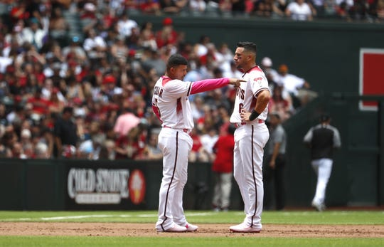 Diamondbacks' David Peralta (R) and Eduardo Escobar talk during a game against the Braves at Chase Field in Phoenix, Ariz. on May 12, 2019.