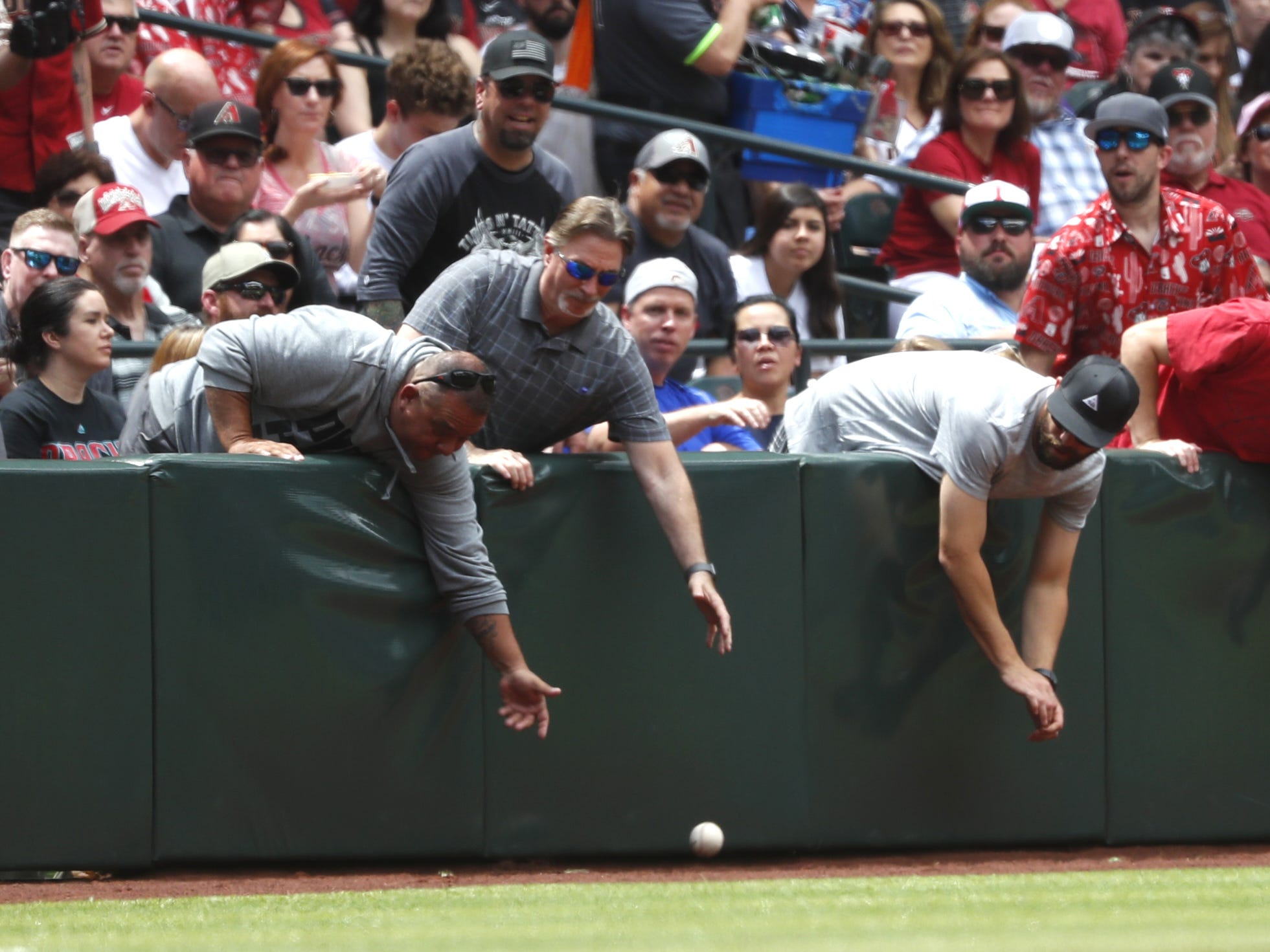 Fans try to grab a foul ball during a Diamondbacks game against the Braves at Chase Field in Phoenix, Ariz. on May 12, 2019.