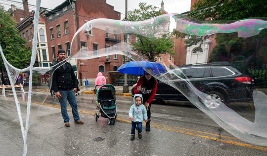 Layla Kroener, front with her parents Chris, left, and Shilyannae, is fascinated by giant bubbles in the Kid's Fun Block during the 44th Annual Olde York Street Fair.