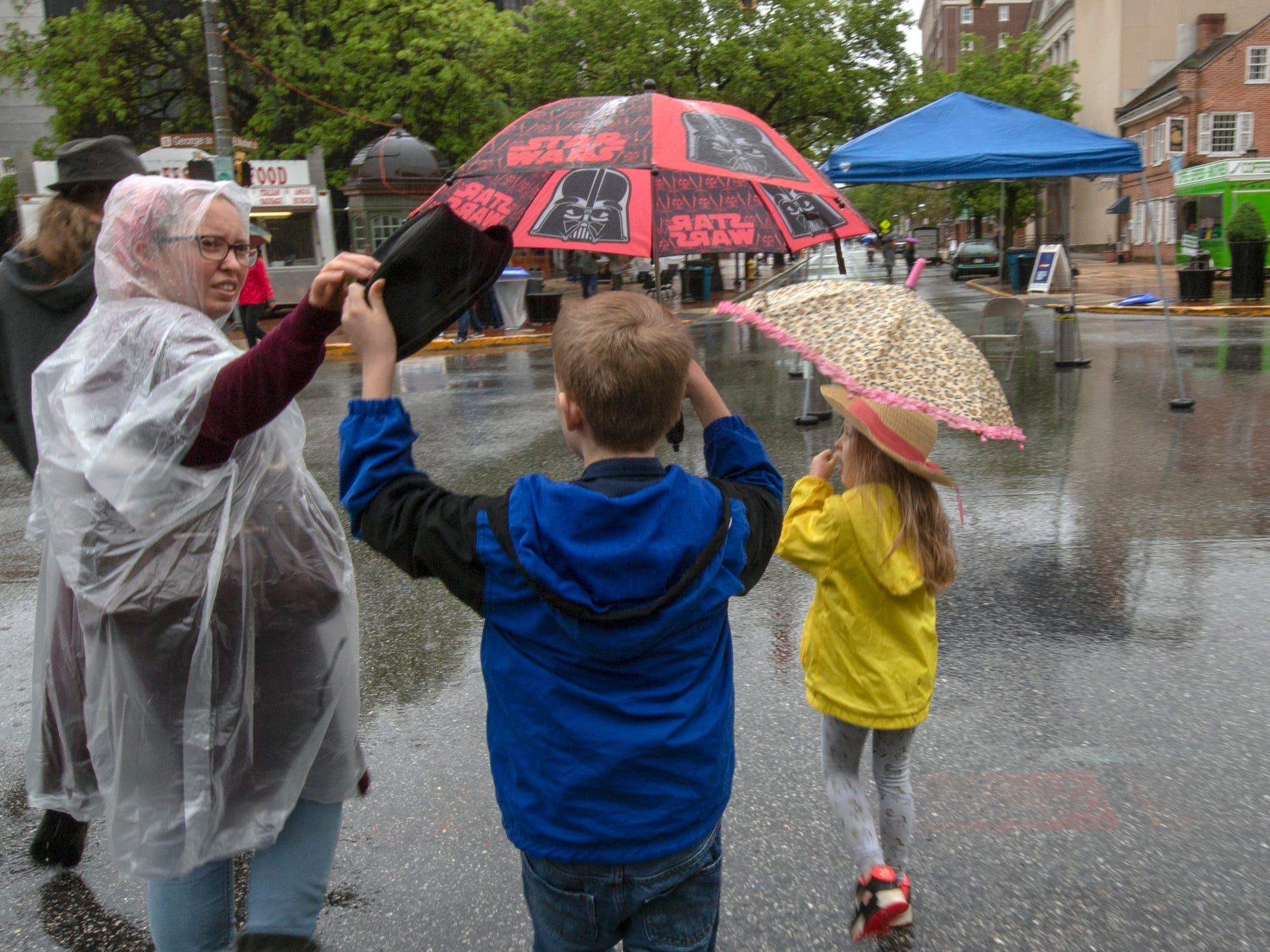 A family adjusts hats and umbrellas during the 44th Annual Olde York Street Fair.