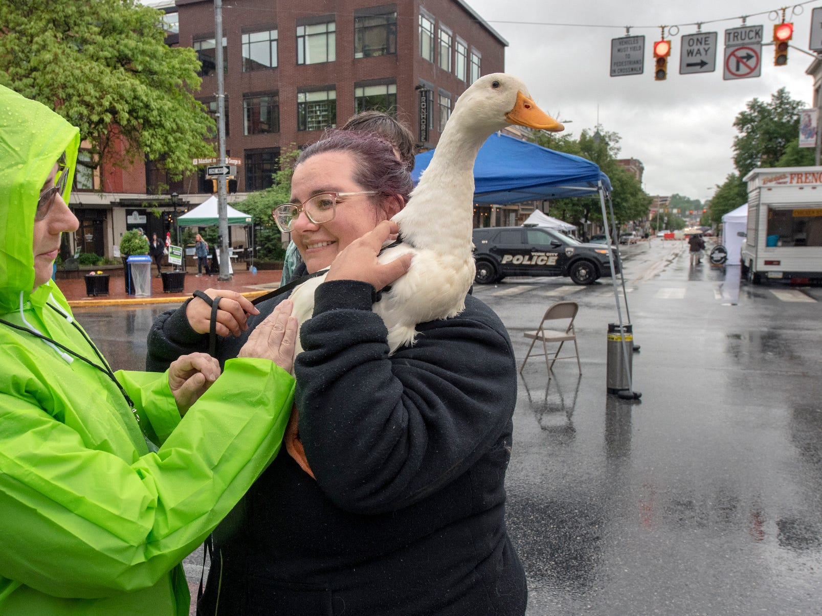 Mary Yeaple, event planner, pets Phil the duck held by Nicole Pauling during the 44th Annual Olde York Street Fair. Phil was part of the Atomic Bounce petting zoo featured in the Kid's Fun Bock. Pauling said that Phil was very interested in the puddles.