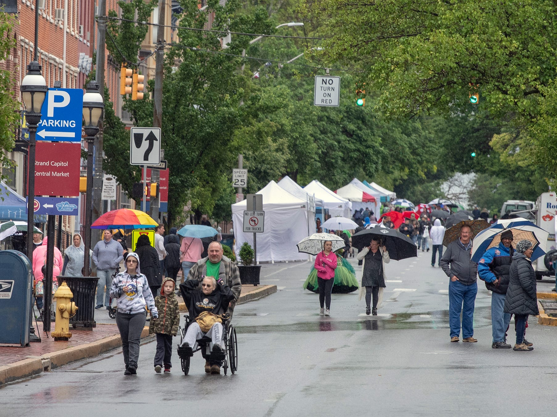 People armed with umbrellas walk in the first block of East Market Street during the 44th Annual Olde York Street Fair.