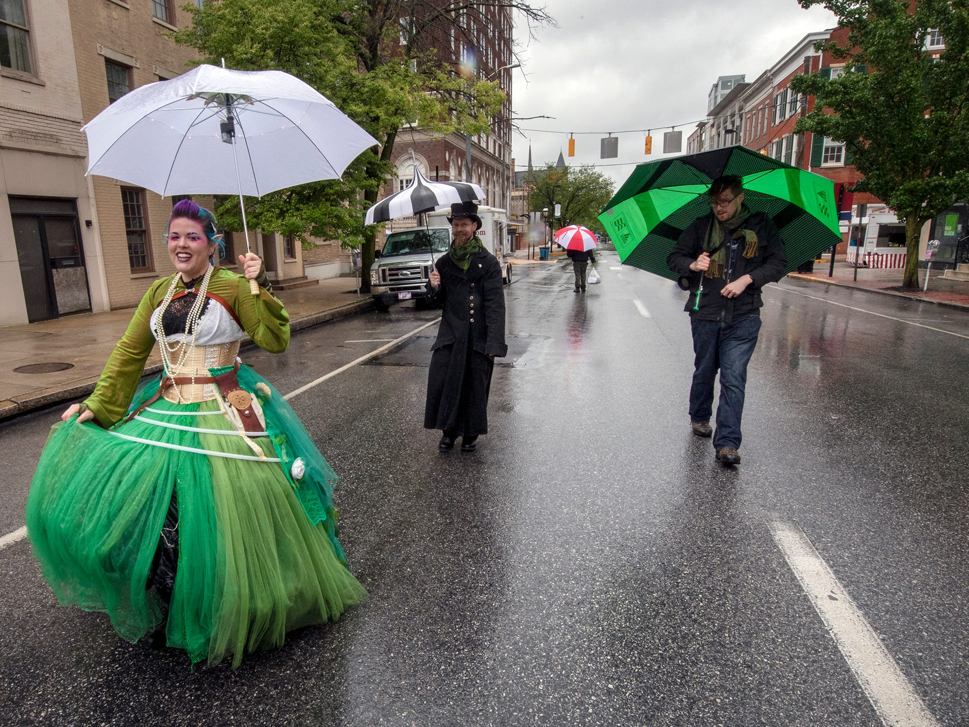 Umbrella clad performers stroll down East Market Street during the 44th Annual Olde York Street Fair.